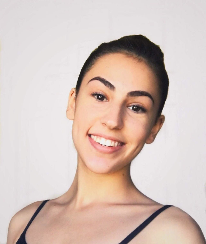 Image Description: Camille is in front of a light, plain backdrop, smiling at the camera. Her dark brown hair is pulled back in a bun and she is wearing a top/leotard with thin black straps.