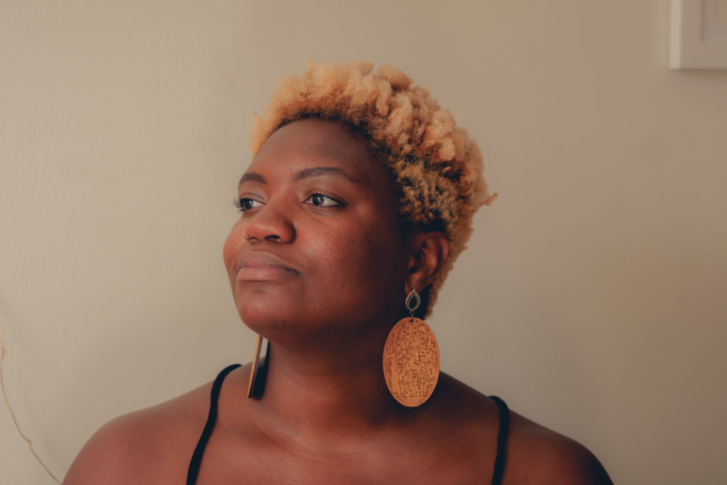 Photo credit: Chidozie Ekwensi. Image description: Photo of a dark skinned Black woman staring towards the light, with her head tilted upwards at an angle. She has short curly blonde hair and wears large wooden earrings