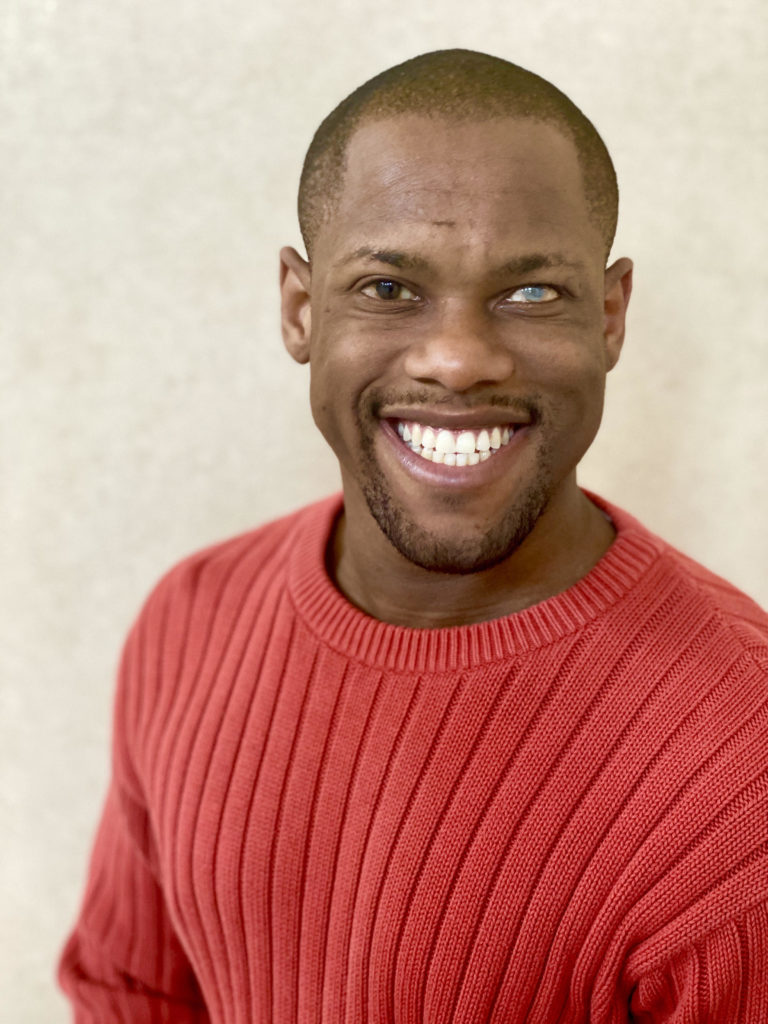 Image Description: Headshot of Telephone artist Davian Robinson. He is smiling and wears a red sweater and is in front of a light background.