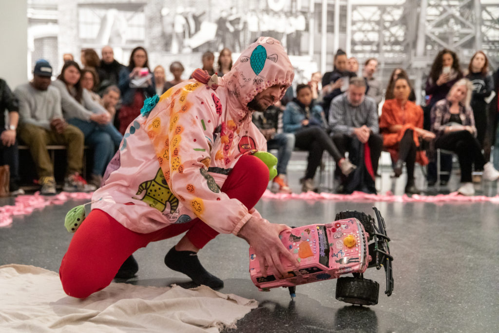 Image Description: Christopher is crouching and holding a pink-painted remote control car. His costume is a pink hoodie and red pajamas. Behind is the audience paying close attention to his performance. Photo credit: Walter Wlodarczyk, courtesy of the Immigrant Artist Biennale.