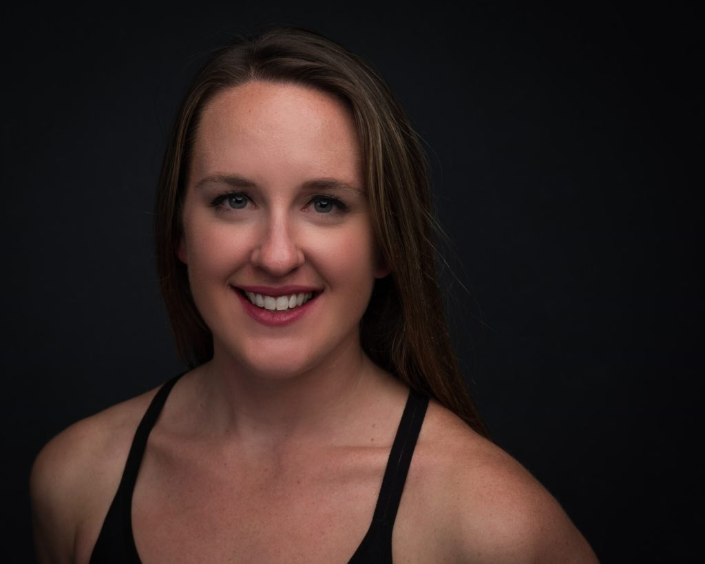 Image Description: Jessica smiles at the camera against a black backdrop. Her long hair is down and she wears a black athletic tank top.