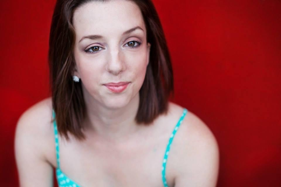 Louisa smiles for the camera; she has straight auburn hair, pale skin, brown eyes and arched brown eyebrows. She is wearing a turquoise blue camisole and poses against a red background.