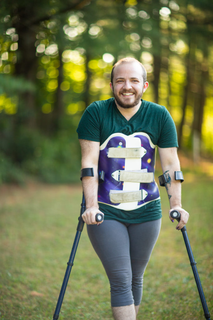 Image description: Toby, a short, broad-shouldered white person with a buzzed head and short dark beard, stands casually leaning into their forearm crutches, a galaxy-print back brace over their leggings and t-shirt. They are outdoors, with a backdrop of soft-focus trees in summer greens and golds. They are smiling directly toward camera.